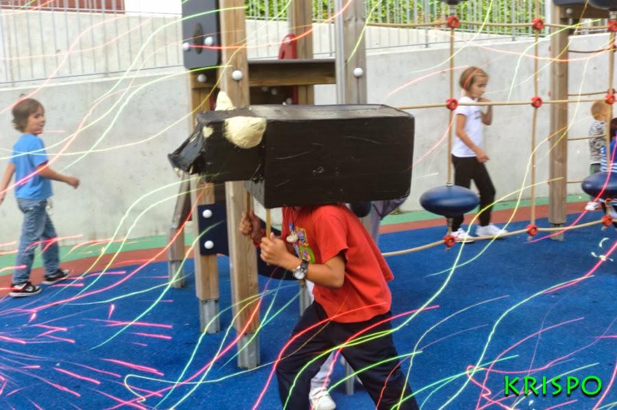 toro de cabezudo persiguiendo niños en parque infantil