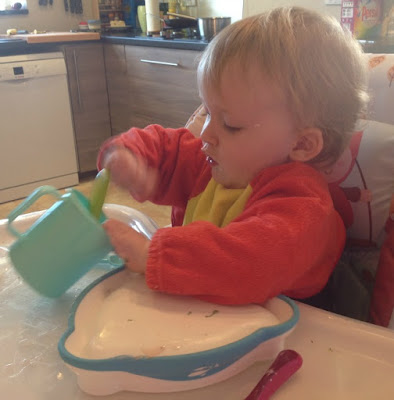 toddler in highchair happily stirring cup with spoon