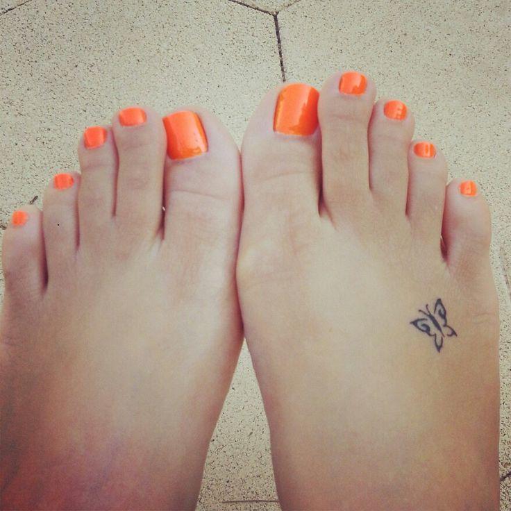 vemos los pies de una chica, con las uñas naranjas, lleva el tatuaje de una mariposa pequeña