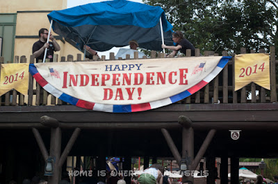 """A """"Happy Independence Day"""" sign hangs over a balcony in Frontierland, Magic Kingdom"""