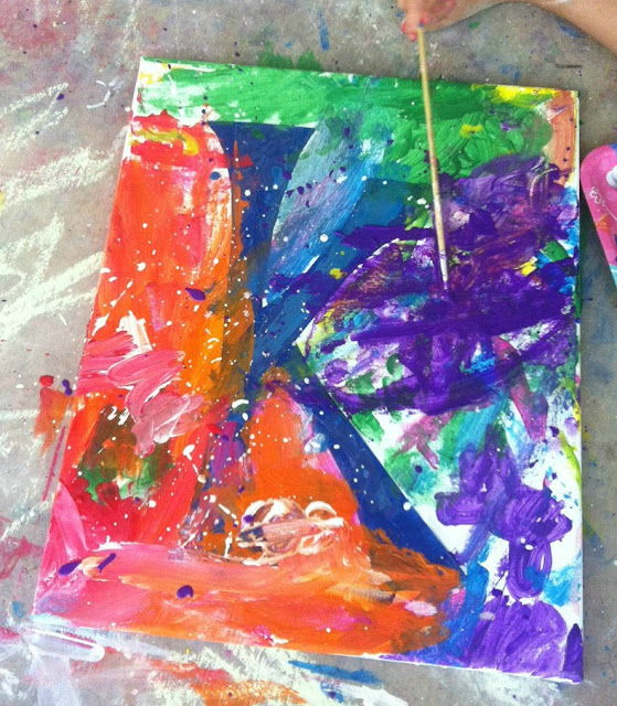 """canvas with the letter """"K"""" taped off mostly painted on in various colors"""