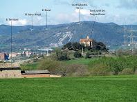 Al davant la capella de Sant Jordi de Puigseslloses i al fons l'església de Sant Sebastià damunt un turó