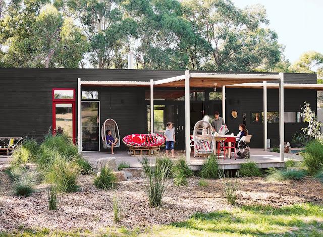 Prefab-Haus aus drei Holz-Modulen mit überdachten Terrassen für Gartenmöbel