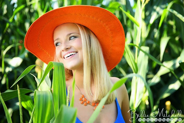 senior girl with orange hat laughing in corn field