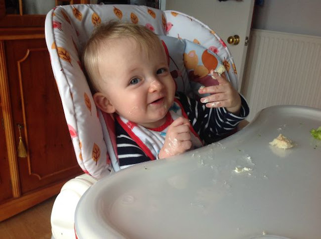 Baby in highchair eating food on face and hands