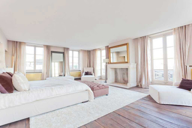 bedroom with wood floor, white shag rug, fireplace with a large mirror with a gold frame above the mantel, french doors and windows with pale pink floor length curtains
