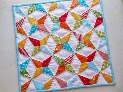 a brightly colored doll quilt with a kaleidoscope design and handstitching