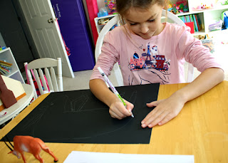After selecting a plastic antelope as a model, Tessa first sketched her design onto warm-up paper and then a sheet of black poster board.