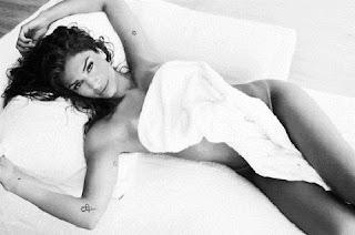 A atriz postou no Instagram foto só com uma toalha cobrindo suas partes íntimas e mostrou uma marquinha de biquíni indiscreta. A loira também exibiu suas tatuagens.