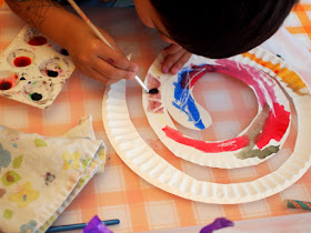 boy using liquid watercolors to paint paper plate snakes