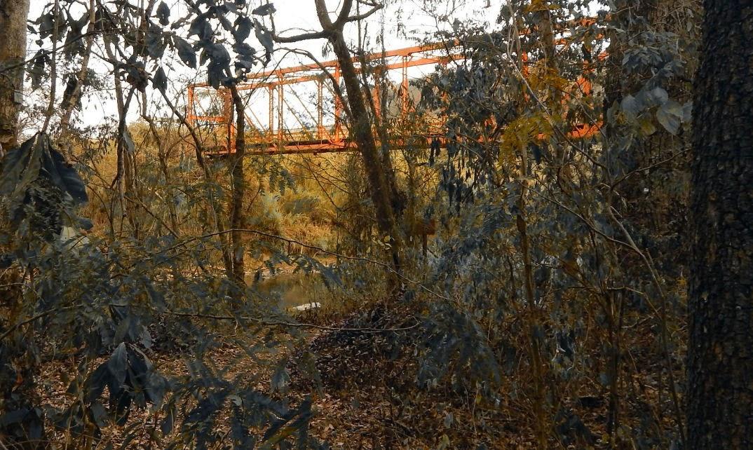 Aos poucos a visão da ponte vai se descortinando por detrás das árvores e folhas secas. Um clima de mistério é embalado nos sons das águas correndo pelas pedras do leito do rio, até que se avista uma escadinha improvisada para descer a barranca que dá acesso a uma pequena praia.