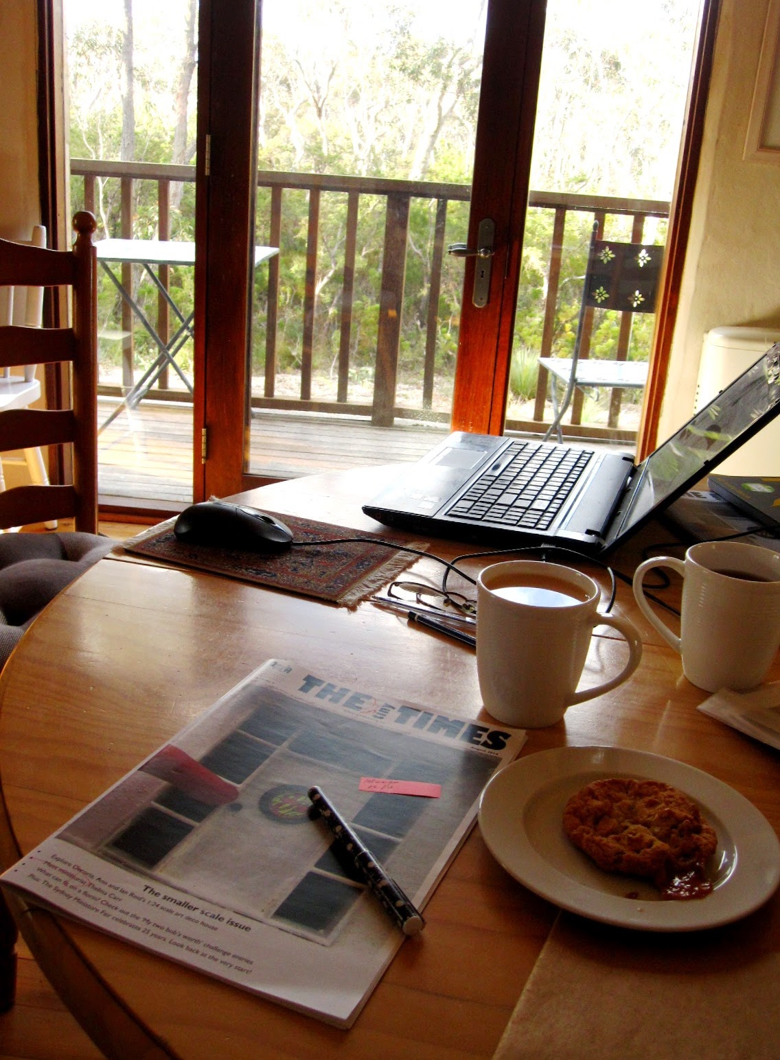 Dining table with two mugs of tea, a biscuit on a plate, a magazine with a pen on it and a laptop in the background.