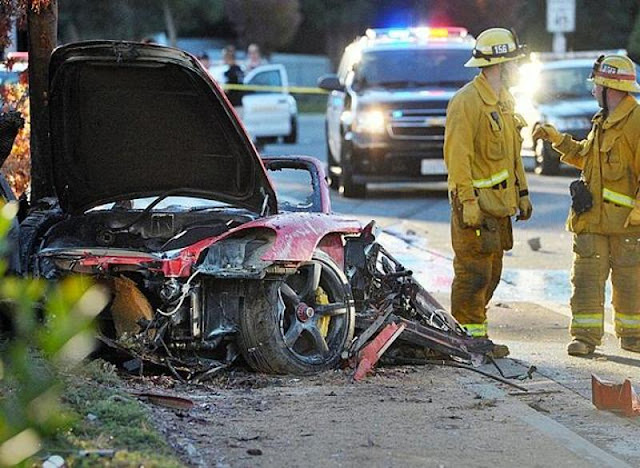 In this file photo, firefighters work next to the wreckage of a Porsche that crashed into a light pole killing actor Paul Walker and his friend Roger Rodas in Valencia, Calif. Crash investigators have determined that the Porsche was travelling approximately 90 mph when it lost control on a city street and smashed into a light pole, killing the actor and his friend. (AP)