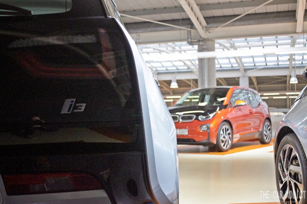 silver BMW i3 badge and an orange i3 in the back