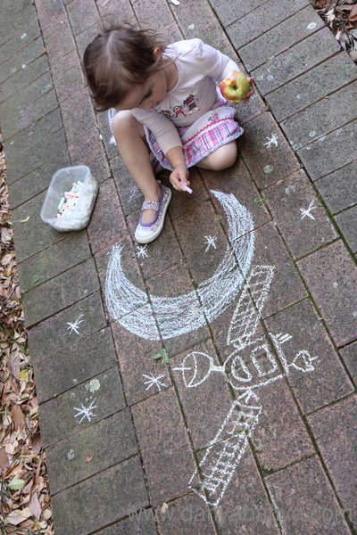 Space chalk drawings of a satellite, the moon and some stars