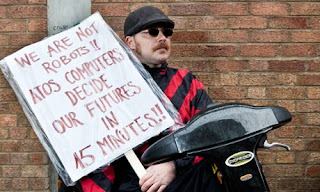 "A man wearing dark glasses and seated on a mobility scooter holds a placard reading ""We are not robots!! ATOS computers decide our futures in 45 minutes""."