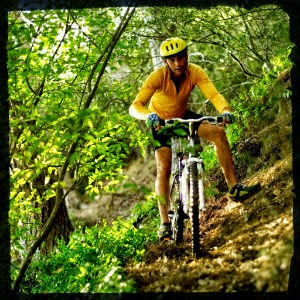 image of a man going mountain biking in a forest
