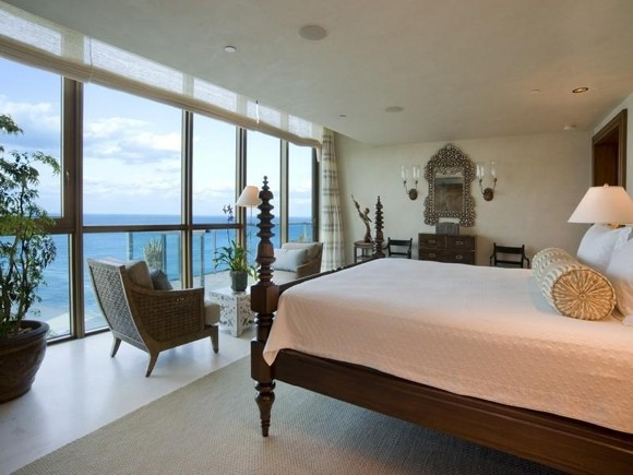 Photo of bedroom with wooden bed and wooden chairs along with the ocean view