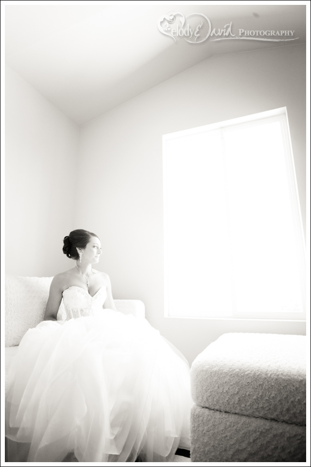 Bride looking out window in black and white