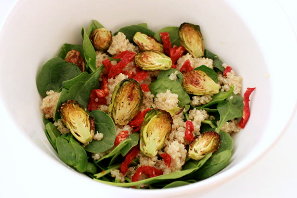Spinach salad with roasted Brussels sprouts, quinoa & sun-dried tomatoes