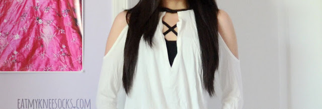 Close-up of the cold shoulder keyhole cutout leather-trim choker-style blouse from SheIn, modeled with a caged strappy bralette.