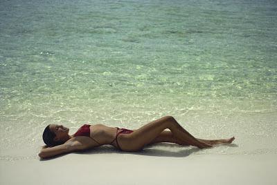 """Cette image montre une superbe jeune fille sexy en bikini rouge étendue sur une plage de reve. Le sable est fin est doré et la mer d'un bleu clair magnifique.  Cette photo illustre le poeme du Marginal Magnifique intitulé «Sur l'oreille», dans lequel le poete raconte sa rencontre avec une jolie jeune fille très excitante au corps de reve qu'il a aborde sur la plage. Le Marginal Magnifique exprime avec humour le désir puissant et irrépressible qu'il a ressenti pour cette jolie creature, si jeune en apparence, mais neanmoins majeure. Il parle ensuite avec beaucoup d'auto-dérision du fait que la jeune fille en question, objet de son désir et de sa convoitise, s'est refusée à lui, ne lui accordant même pas de toucher ses pieds pour enlever le sable collé par l'eau de mer. Le titre du poeme s'explique par ce refus de la jeune fille magnifique de céder aux avances du dragueur-poete: il est le raccourci de l'expression """"se la mettre derrière l'oreille"""" ou """"sur l'oreille"""" qui signifie ne pas parvenir à niquer une fille, pour être clair mettre sa bite derrière son oreille, tristement inemployée et strictement inutile, plutôt que dans le vagin de la fille."""