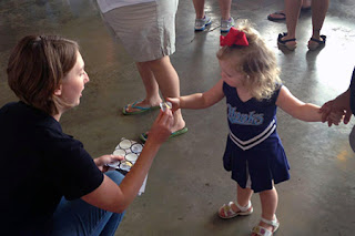 Shannon Posern (l) gives a sticker to a young girl as part of the Take 25 program.