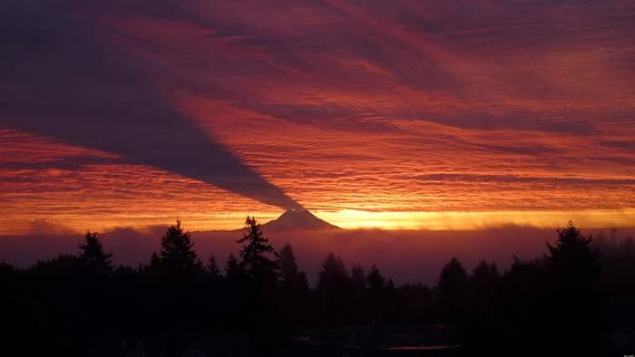 The shadow of Washington state's Mt. Rainier cast along the clouds at sunrise.