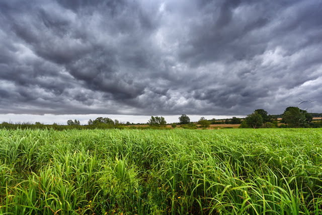 Rural Oxfordshire field with dark stormy clouds above by Martyn Ferry Photography