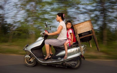 Five-year-old Lu Siling rides with her desk on the back of her mother's motorbike on the first day of school in Macheng, China. There are 5,000 pupils at the schools in the town, but only about 2,000 desks. So more than 3,000 children have to go to school with desks and chairs, like their parents' generation. Some children even use their parents' old desks.Picture: China Foto Press / Barcroft Media