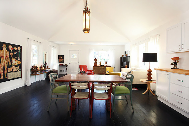 Dining room with stained wood floor, wood table, mismatched chairs, a pendant light and an anatomy poster