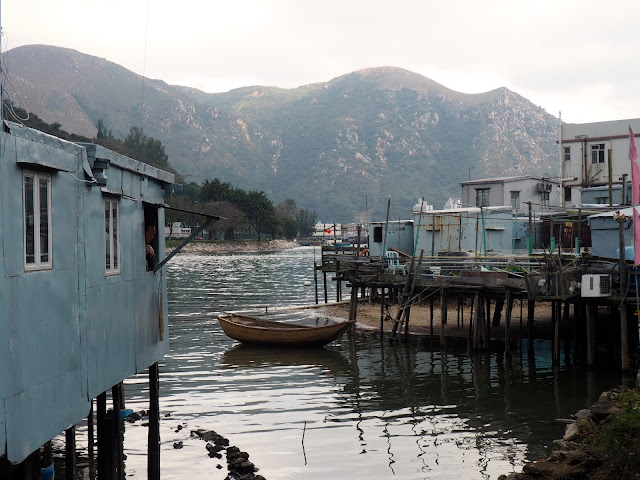 Stilt houses and a lone fishing boat at Tai O fishing village, Lantau Island, Hong Kong