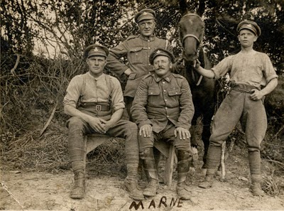 Four soldiers of the 7th Battalion, Durham Light Infantry, including Corporal George Thompson, standing left, and Sergeant 'Twankey' Tweddle, seated right, and horse in a field at Marne, July 1918 (D/DLI 7/700/31)