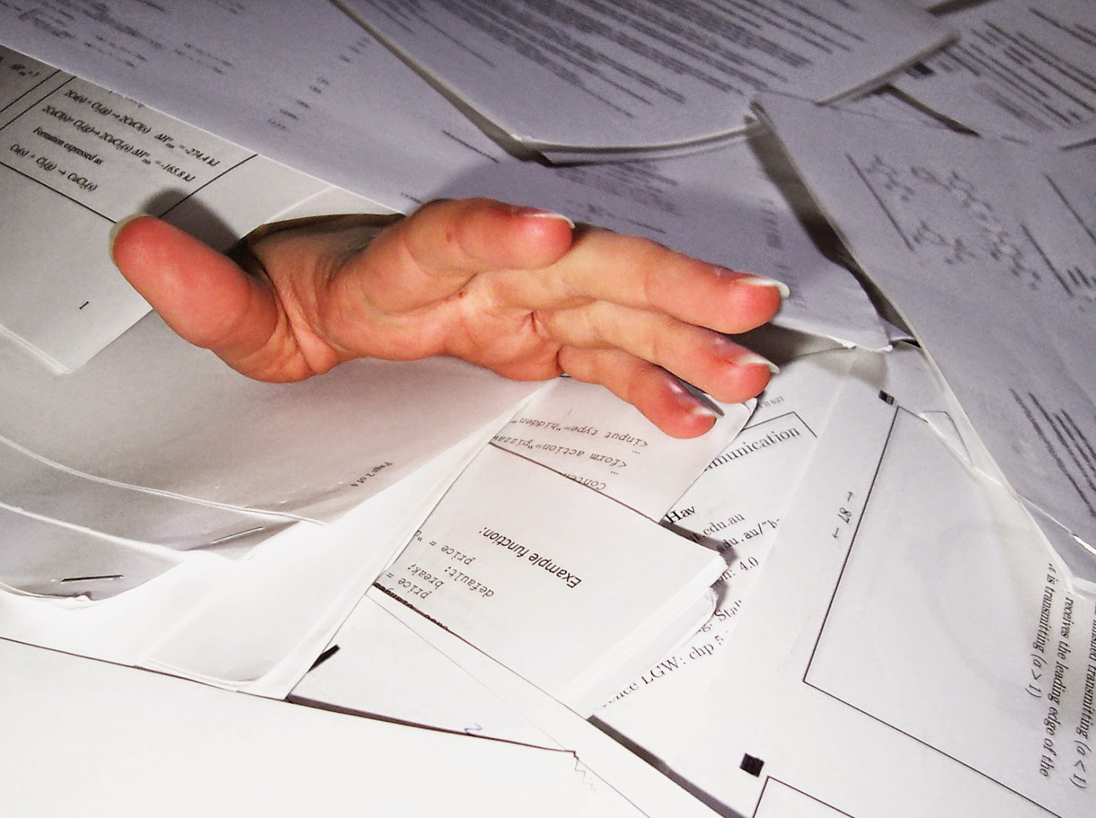 A hand reaching out of a huge pile of papers