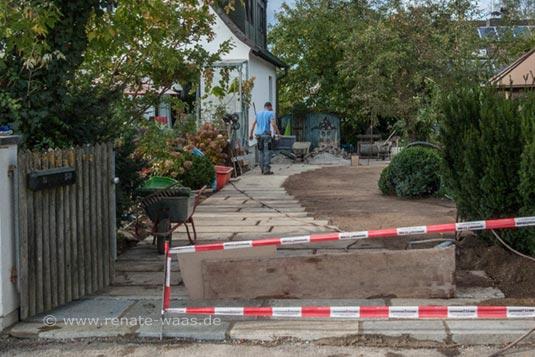 Die Granitplatten sind gelegt und die Flächen für den Schotterrasen eingesät.