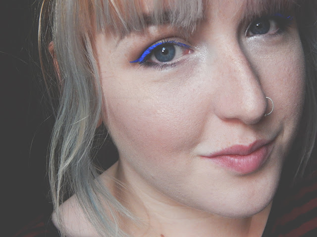 Girl smiling with bright blue winged eyeliner