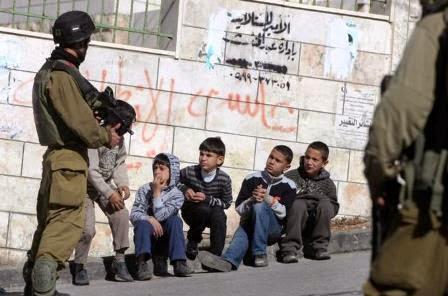 soldados israelense vigiam crianças feitas prisioneiras