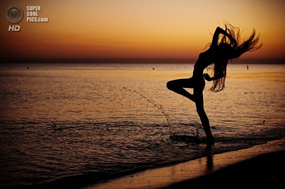 Фото силуэт девушки которая стоит на берегу моря