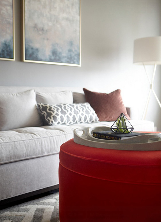 A bold red ottoman breaks the subtle monotony in this living room designed by Niche Interiors.  Photo by Thomas Kuoh.