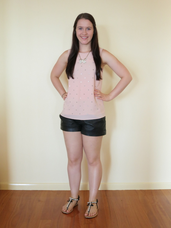 Leather shorts, a blush embellished top with sandals and a sparkly bow necklace.