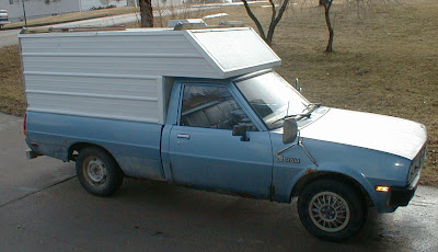 Old small pickup truck with homemade topper