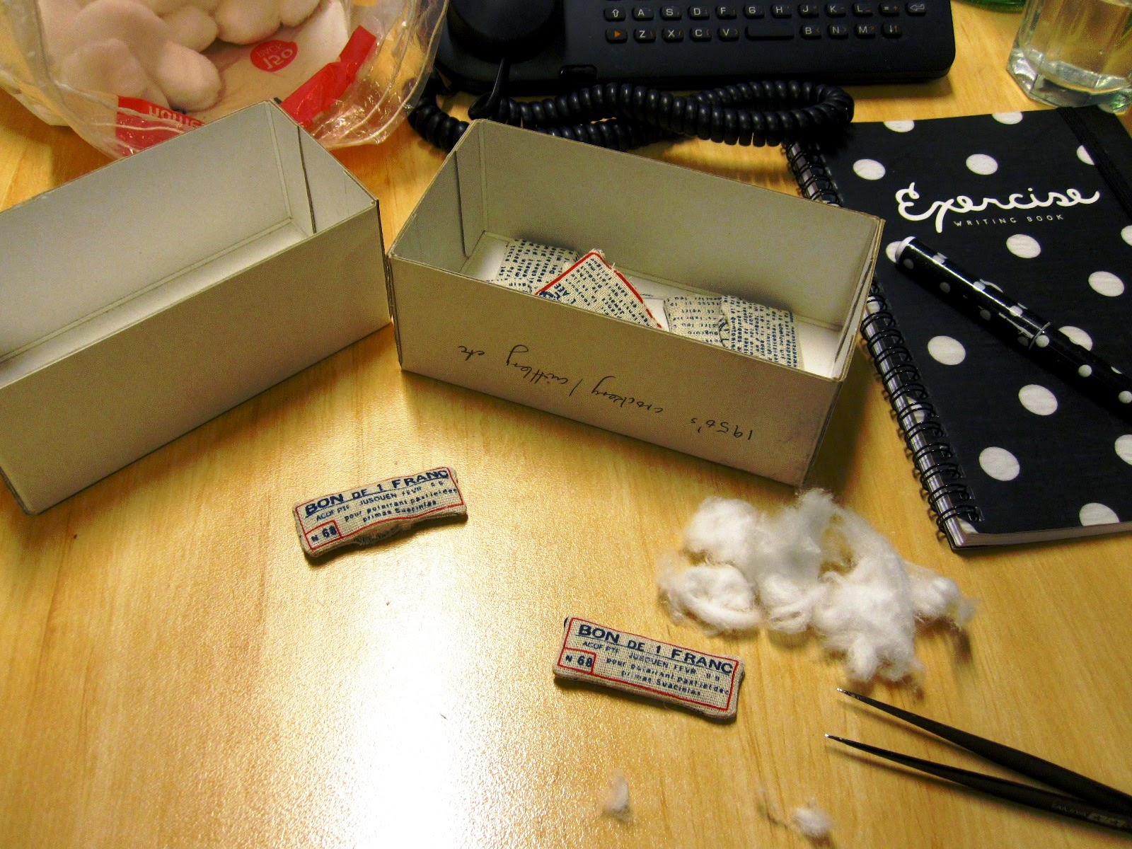 Office desk with unstuffed dolls house miniature cushions, cotton balls and tweezers.