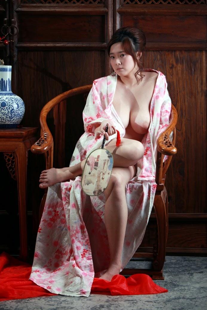 asiatique en kimono ouvert sur sa nudité assise sur une chaise un eventail à la main