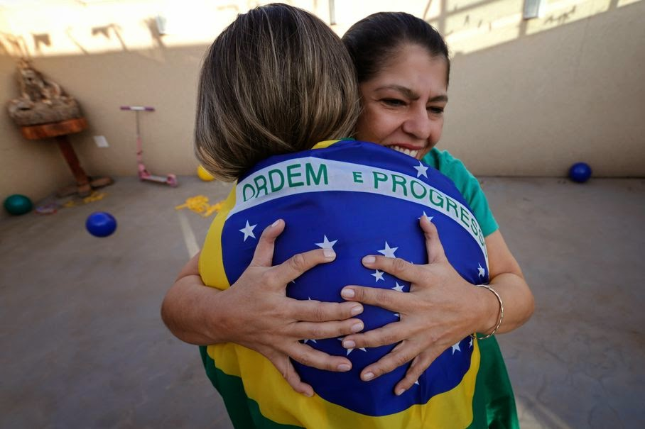 Silvia Santos, facing camera, embraces her daughter Ana Carolina at their home in Brasilia, Brazil, Thursday, June 19, 2014. All the members of the Silva family were born with an extra digit on each hand as a result of a genetic condition known as polydactyly. Rather than recoil in the face of constant stares by curious onlookers the 14 members of the family spanning four generations seem to embrace their physical differences with pride.