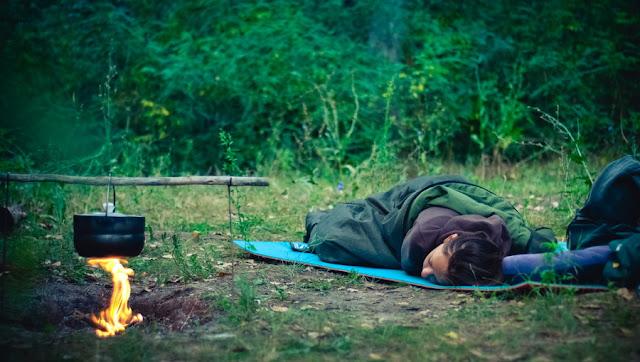 Девушка спит рядом с костром