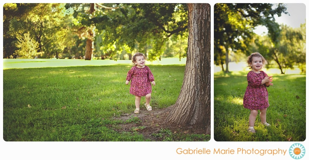 Fun 18 month girl playing in a park wearing a pink dress.