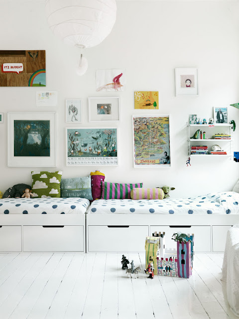 Kid's bedroom with white beds with white bedding with blue spots, white under bed storage cabinets and framed pictures from a variety of children's books
