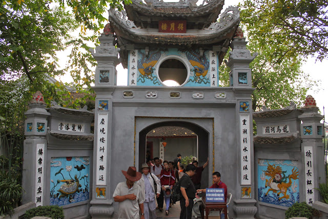 The entrance of Ngoc Son Temple after crossing the famous red Huc Bridge at Hoan Kiem Lake in Hanoi, Vietnam