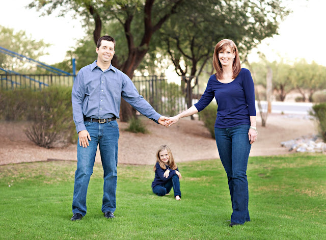 Oro Valley Mom and Dad holding hands with child sitting in the grass in the background