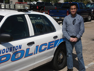Yzquierdo poses in front of a Houston Police Department patrol car.